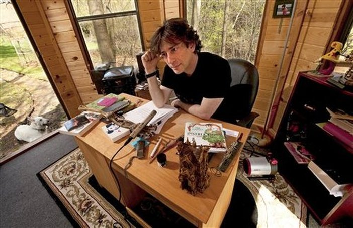 Neil Gaiman Writes On A Desk That Is Being Described As Scarcely Bigger Than TV Tray